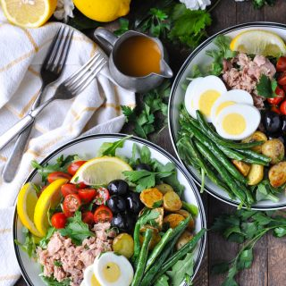 An overhead shot of two bowls filled with tuna nicoise salad