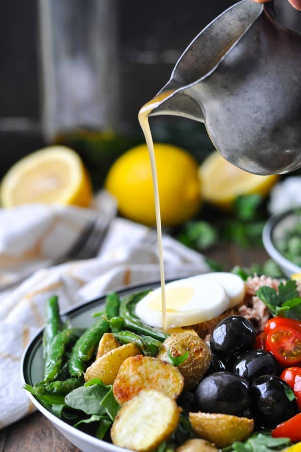 Pouring homemade vinaigrette over a Tuna Nicoise Salad