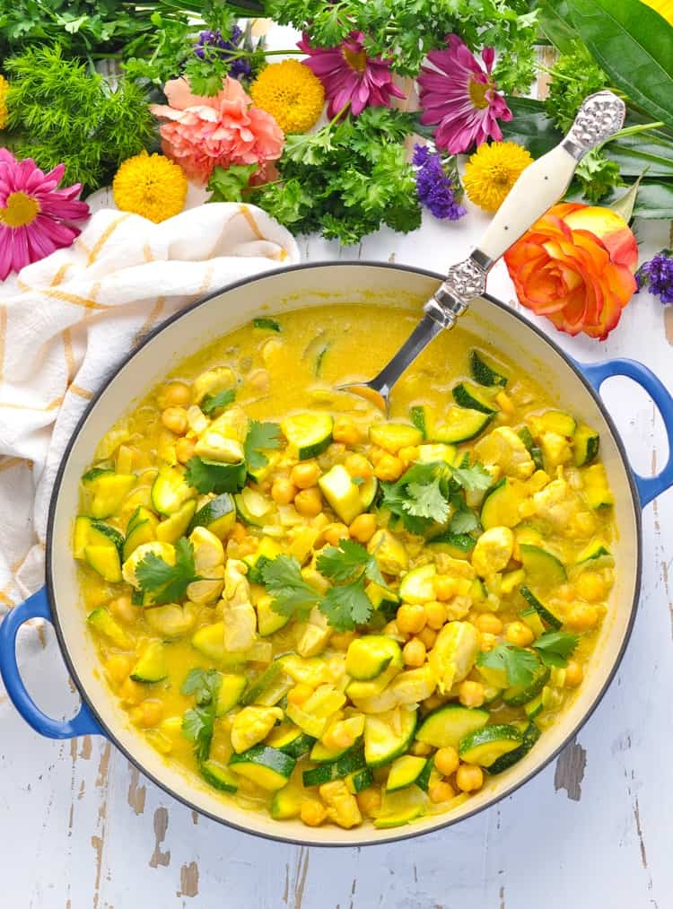 Overhead image of one pot coconut chicken curry with zucchini and chickpeas.