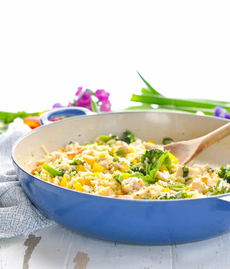 Blue skillet with an easy dinner recipe for chicken and rice with fresh vegetables