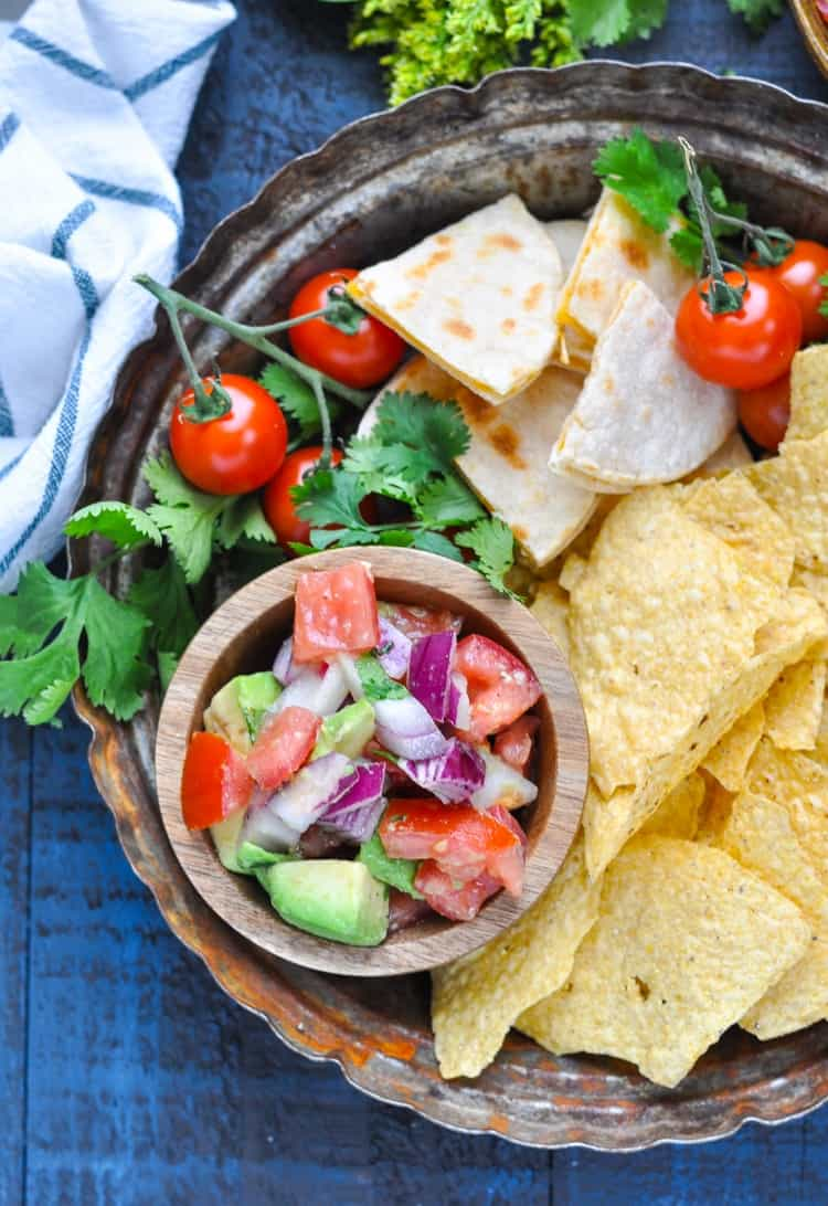 Overhead image of pico de gallo on a tray with cheese quesadillas and tortilla chips