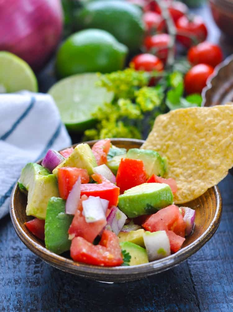 Bowl with easy pico de gallo recipe and tortilla chip for dipping