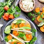 Overhead shot of shrimp tacos on a metal plate with avocado and fresh lime