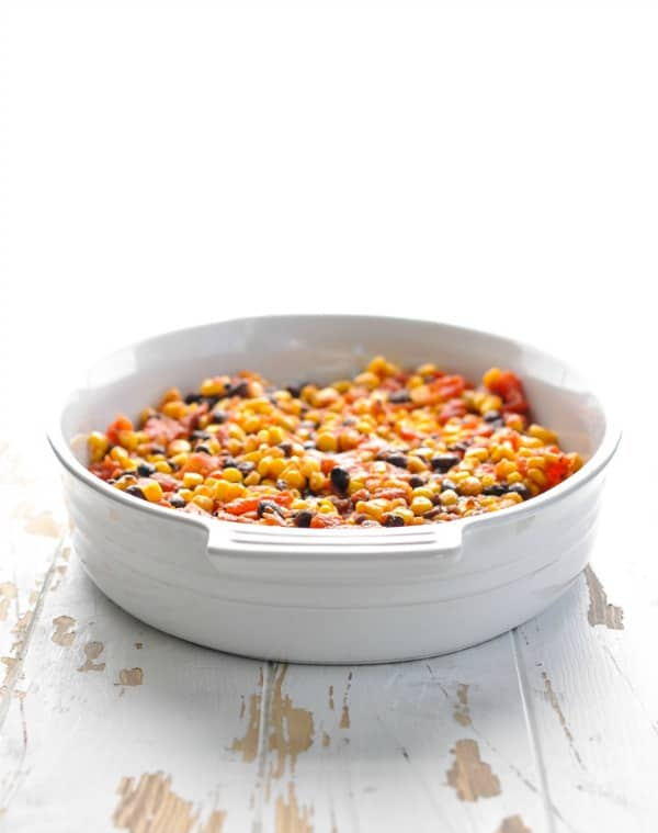 Corn and bean and salsa mixture in bottom of a white casserole dish