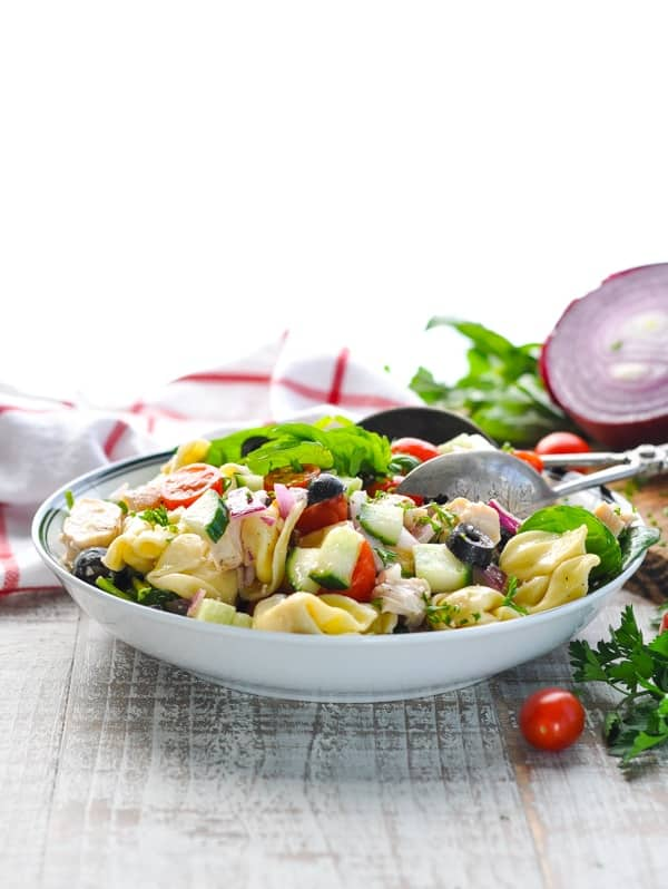 A side shot of a bowl of chicken and tortellini salad with tomatoes sitting on a wooden surface
