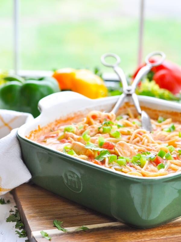 Baked chicken spaghetti casserole in a green dish.