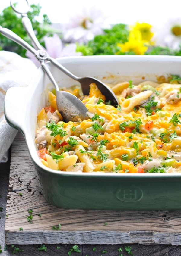 A dump-and-bake creamy chicken penne pasta casserole in a green dish that's topped with cheese and garnished with parsley.