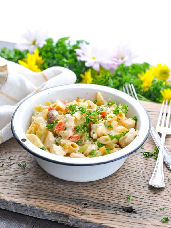 A bowl full of creamy penne pasta with chicken and vegetables.
