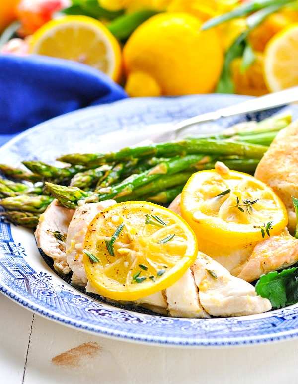 Sliced lemon chicken breast on a plate topped with lemon slices