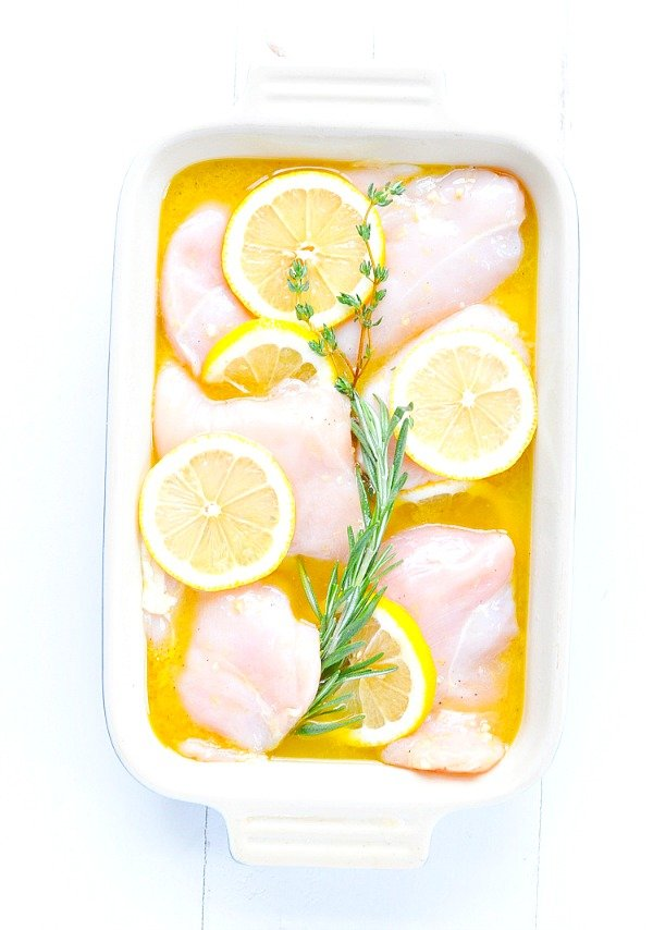 Overhead shot of raw chicken breasts and lemon slices in baking dish