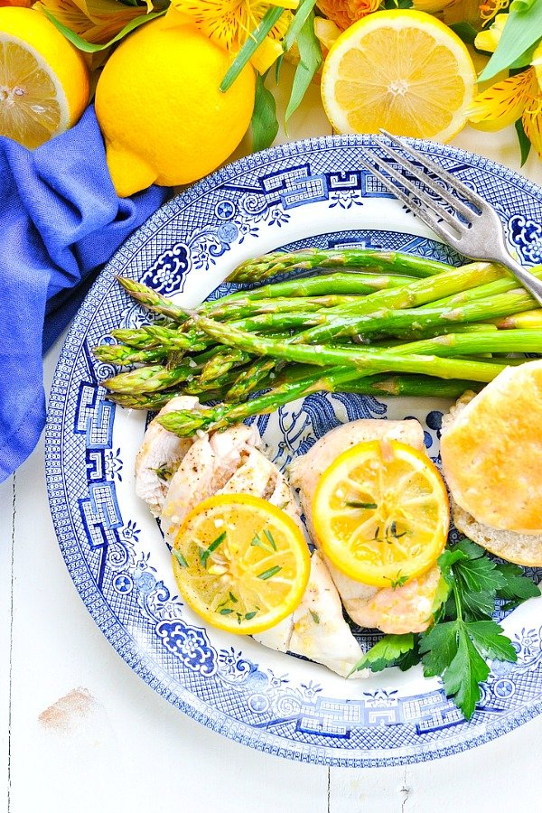 Overhead shot of baked lemon chicken breasts on a plate with asparagus