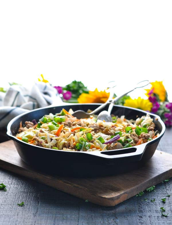 Cast iron skillet full of healthy stir fry recipe called Egg Roll in a Bowl