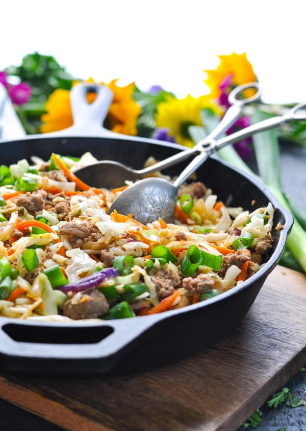 A skillet with a ground beef, ground turkey, or ground chicken recipe and cabbage for a healthy stir fry.