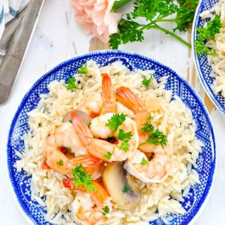 Overhead shot of garlic shrimp on a bed of rice with parsley garnish