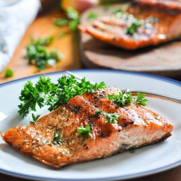 A beautiful piece of grilled salmon on a plate garnished with parsley.