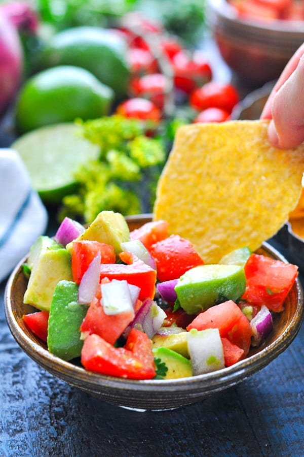 Dipping a tortilla chip into a bowl of pico de gallo
