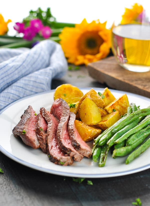 Plate of sliced ribeye steak with potatoes and green beans.