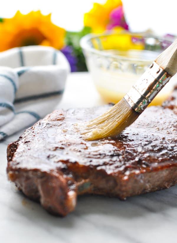 Brushing a ribeye steak with garlic butter