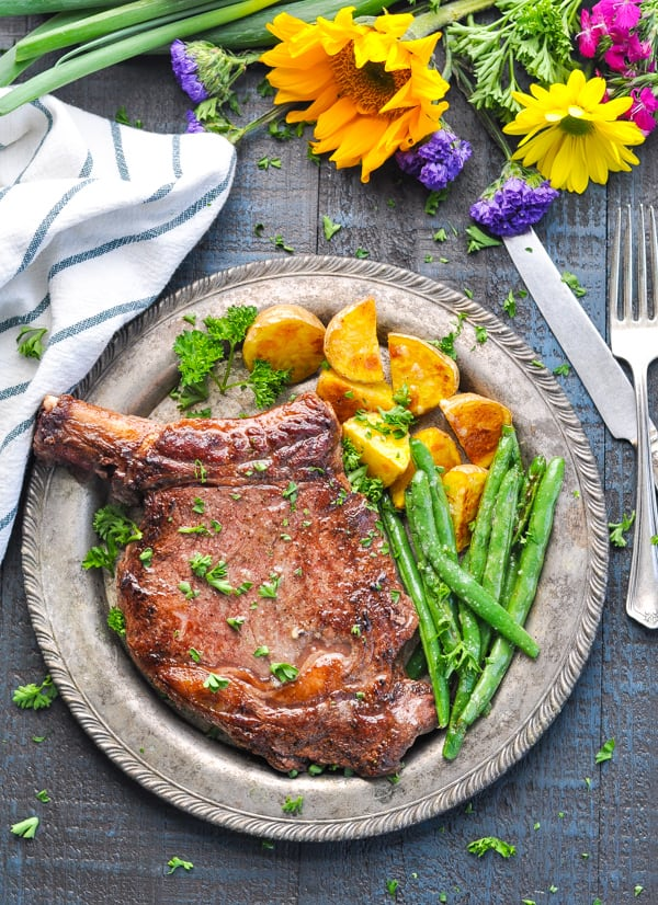 Ribeye steak that has been pan fried and served with crispy roasted potatoes and green beans.