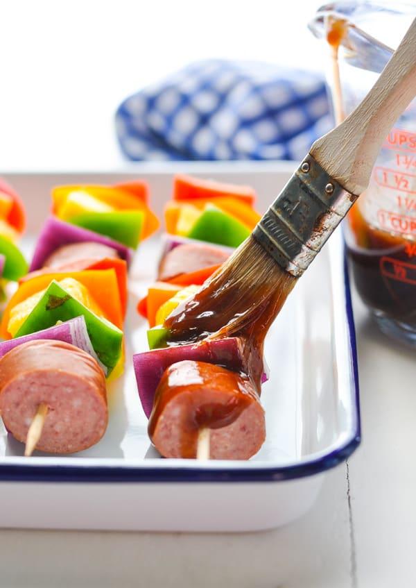 Basting Hawaiian Kielbasa Kebabs with barbecue sauce.