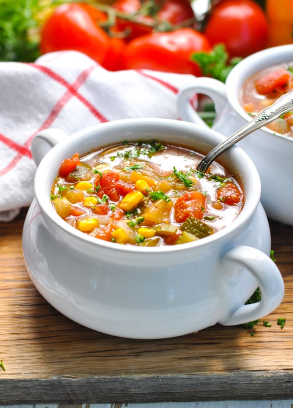 A close up of a white bowl filled with Bowl vegetable soup sitting on a wooden surface