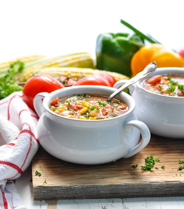 2 white bowls of easy homemade vegetable soup sitting on a wooden board with vegetables in the background