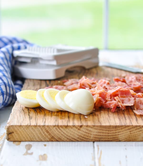 Hard boiled eggs and chopped bacon on a chopping board