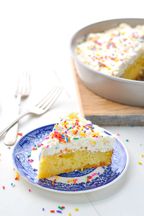 Slice of pineapple orange cake on a blue and white plate with sprinkles on top