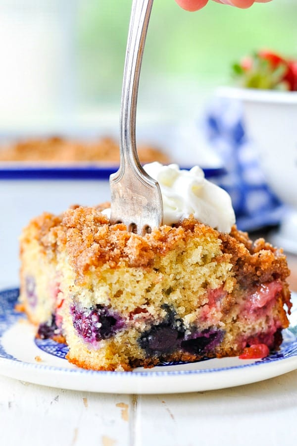 A fork digging into a slice of blueberry buckle cake