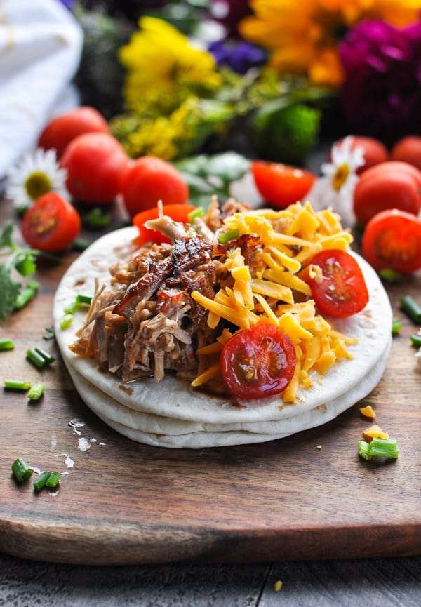 Side shot of crispy slow cooker carnitas on a wooden cutting board