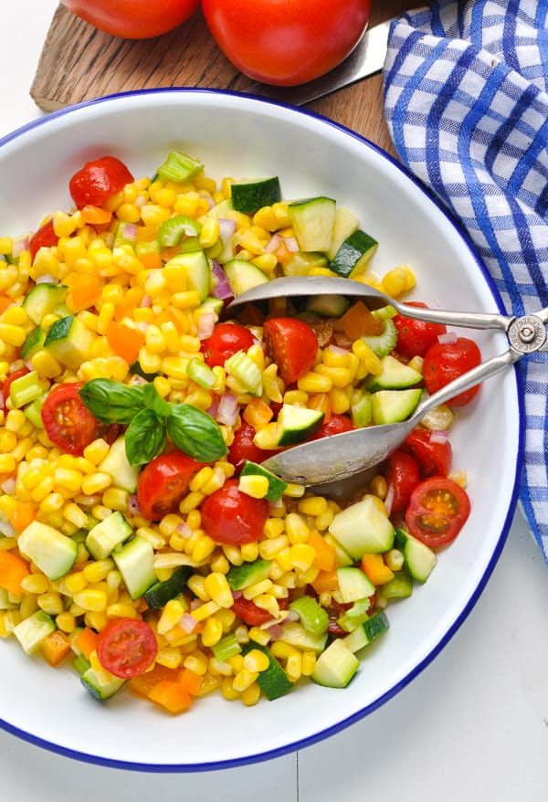 Corn tomatoes bell peppers and zucchini come together in a healthy side dish recipe for corn salad!