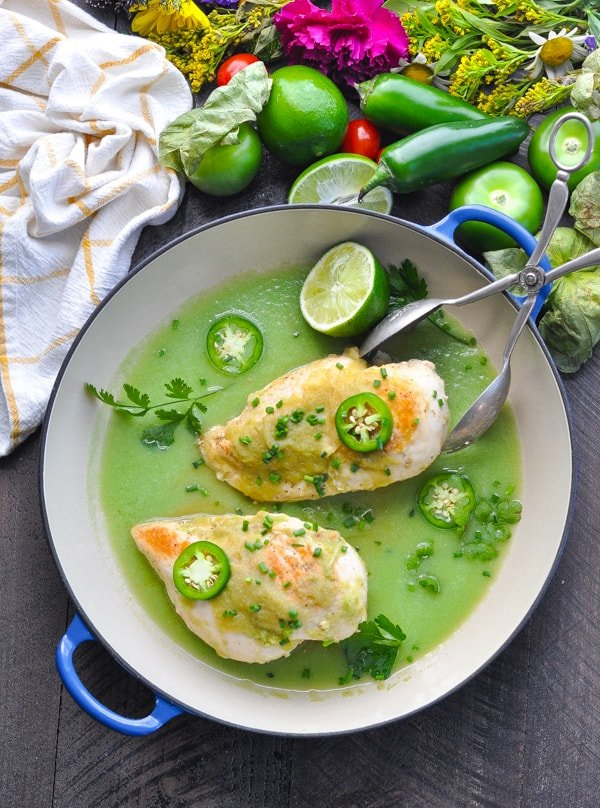 Tomatillo Chicken cooks in a skillet with salsa verde for an easy dinner idea