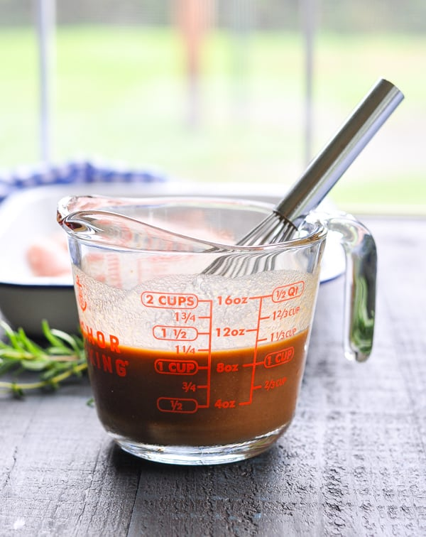 A sauce in a measuring jug for pouring over baked chicken
