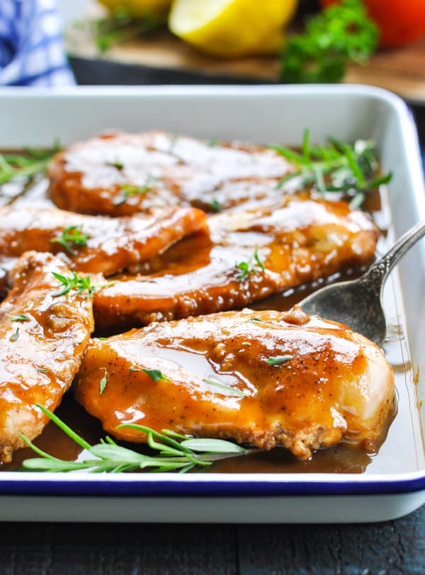 A close up of baked chicken on a baking sheet with herbs