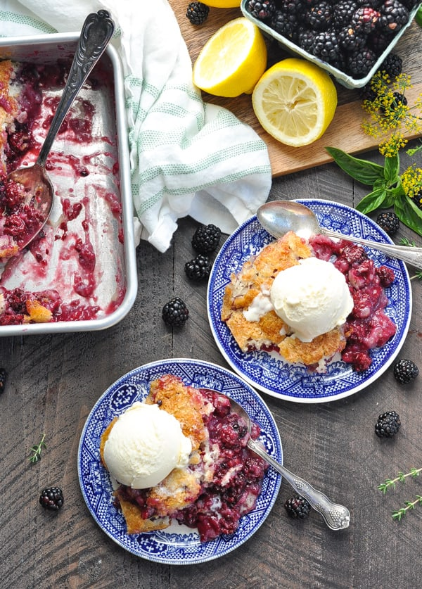 Plates with the best blackberry cobbler and vanilla ice cream with spoons