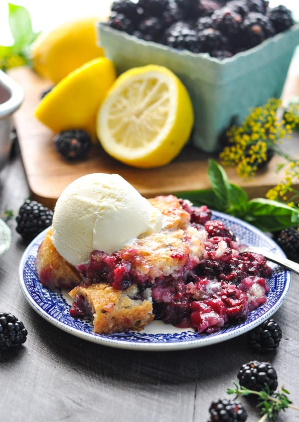 A close up of the best blackberry cobbler on a plate with vanilla ice cream