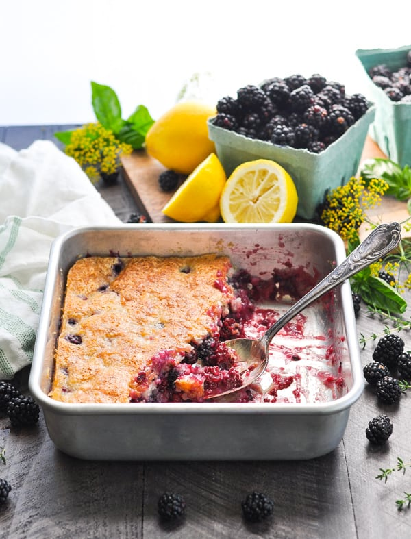 The best blackberry cobbler in a baking dish with a serving spoon