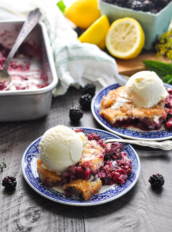 The best Blackberry Cobbler on two small plates with a scoop of ice cream