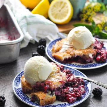 The best blackberry cobbler on a blue plate topped with ice cream