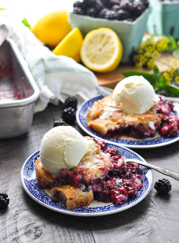 A close up of the best blackberry cobbler topped with vanilla ice cream
