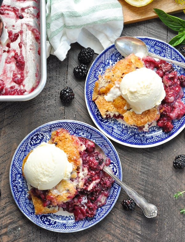 An overhead shot of blackberry cobbler on two plate with ice cream
