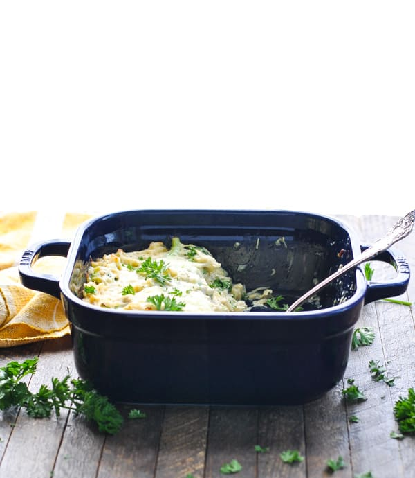 Chicken Broccoli and Rice Casserole in a blue casserole dish sitting on a wooden surface