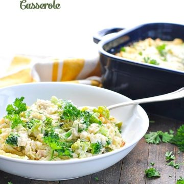 A Chicken Broccoli and Rice Casserole in a white bowl topped with herbs