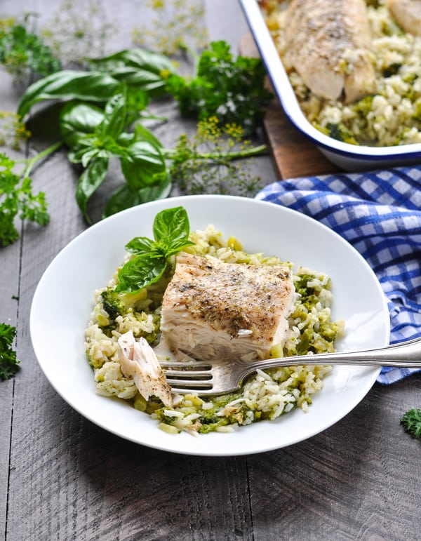 Fish recipe for baked cod or mahi mahi with rice and broccoli on a fork with a white plate