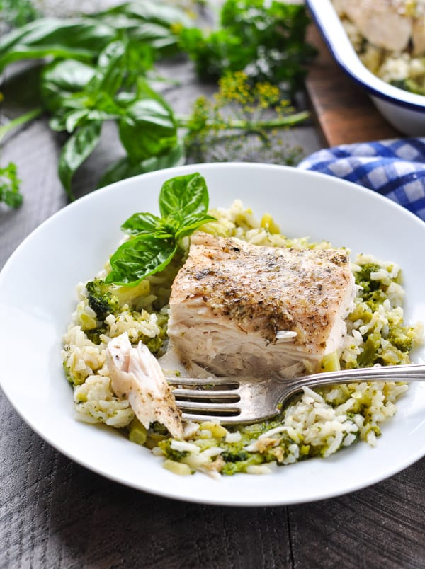 Italian fish with broccoli and rice on a white plate with a fork and fresh basil