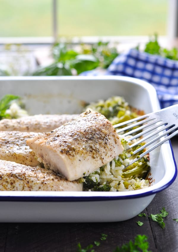 Baked fish with broccoli and rice in a white enamelware baking dish