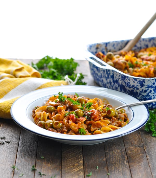 Bowl of Johnny Marzetti Casserole with casserole dish in background