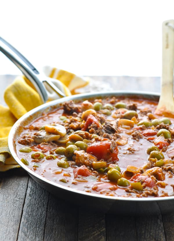 Green olives and mushrooms in Johnny Marzetti casserole in skillet with wooden spoon