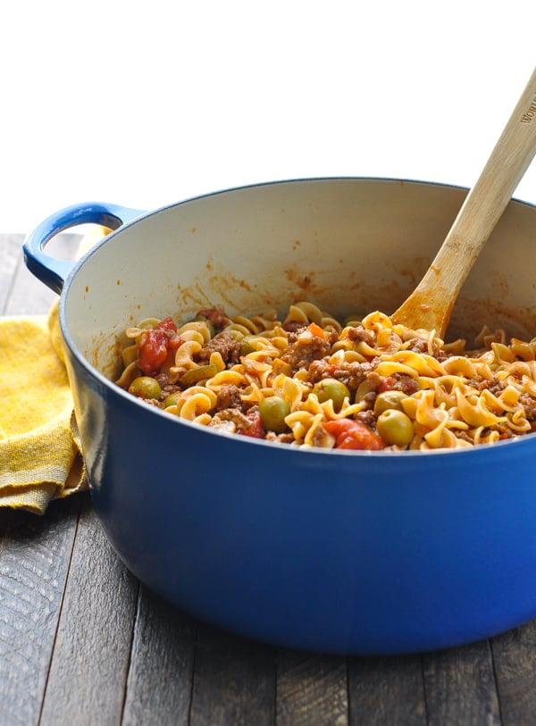 Egg noodles stirred into johnny marzetti casserole in big blue pot