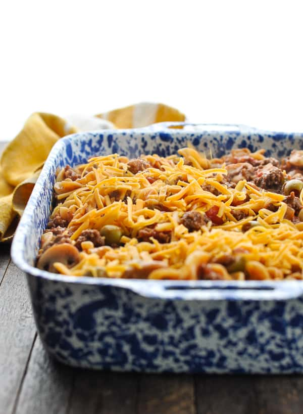 Grated cheddar cheese on top of Johnny Marzetti casserole